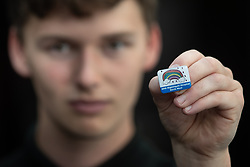 "© Licensed to London News Pictures . 22/04/2020. Manchester, UK. In an echo of Health Secretary Matt Hancock's pose with a ""CARE"" badge , Porter LEWIS MACLENNAN (21) , holds a commemorative badge , being given as a gift to those who have worked at the NHS Nightingale Hospital in Manchester . The National Health Service has built a 648 bed field hospital for the treatment of Covid-19 patients , at the historical railway station terminus which now forms the main hall of the Manchester Central Convention Centre . The facility is treating patients from across the North West of England , providing them with general medical care and oxygen therapy after discharge from Intensive Care Units . Photo credit : Joel Goodman/LNP"