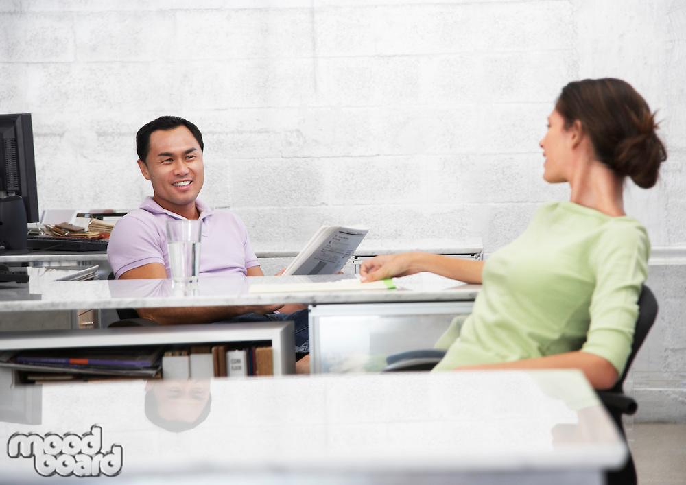 Mid adult man and woman sitting at desks talking