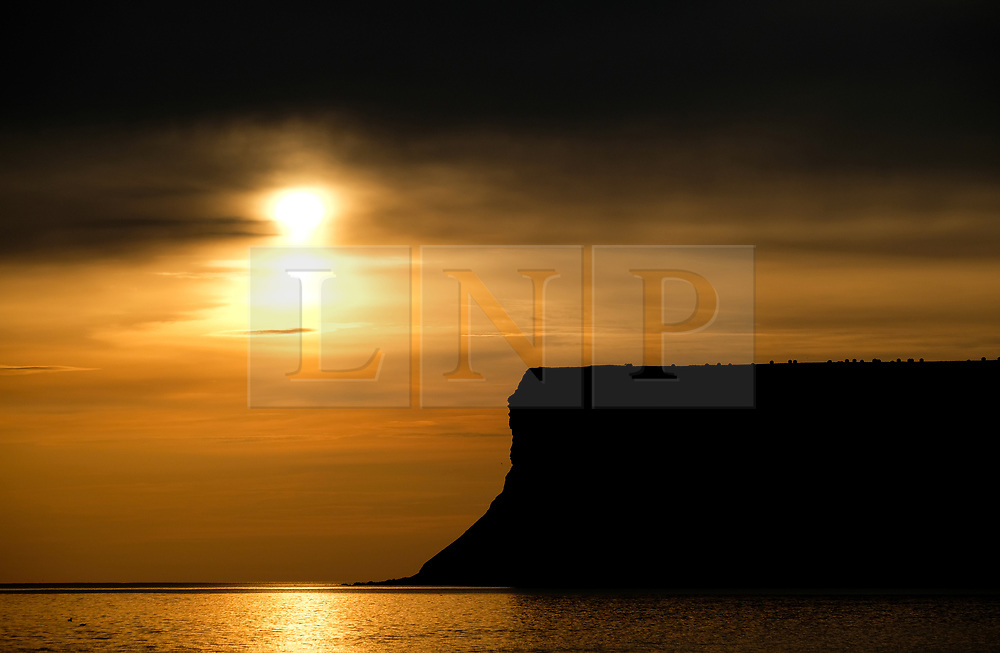 © Licensed to London News Pictures. <br /> 28/08/2017<br /> SALTBURN-BY-THE-SEA, UK.  <br /> The sun rises into clouds over Huntcliff in Saltburn-by-the-Sea on Bank Holiday Monday.<br />   <br /> Photo credit: Ian Forsyth/LNP