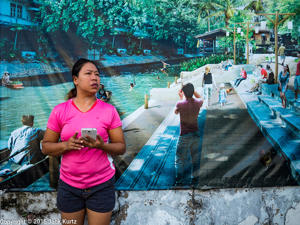 "29 SEPTEMBER 2016 - BANGKOK, THAILAND:  A woman stands in front of an artist rendering of what the residents of Pom Mahakan want to turn their community into - a ""living heritage museum"" that draws both Thai and foreign tourists. The rendering is on the city wall that is the western boundary of the community. Forty-four families still live in the Pom Mahakan Fort community. The status of the remaining families is not clear. Bangkok officials are still trying to move them out of the fort and community leaders are barricading themselves in the fort. The residents of the historic fort are joined almost every day by community activists from around Bangkok who support their efforts to stay.    PHOTO BY JACK KURTZ"
