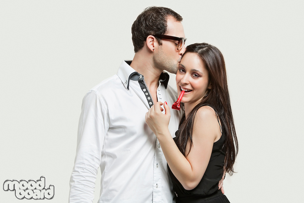 Young couple with party puffer against gray background