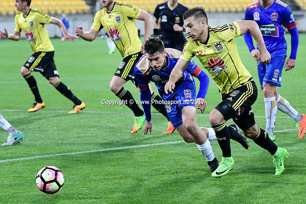 Phoenix's Kosta Barbarises (R with Newcastle's' Aleksandr Kokko fight for possession during the A-League - Phoenix v Newcastle football match at Westpac Stadium in Wellington on Sunday the 26th of March 2017. Copyright Photo by Marty Melville / www.Photosport.nz