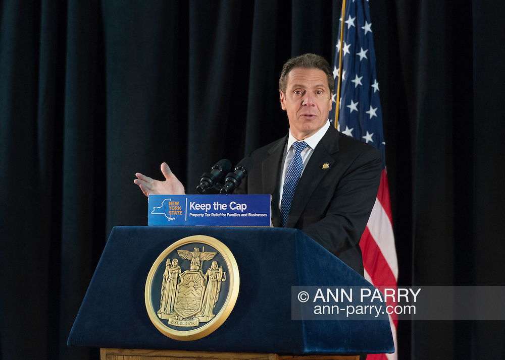 New York State Governor ANDREW CUOMO speaks at an event in support of extending the NY Property Tax Cap. At the bi-partisan event at Knights of Columbus Hall, over a hundred area residents and officials urged an extension of the property tax cap before the state legislative session ends on June 17. The NY Property Tax Cap is set to expire June 2016, but is legally linked to NYC rent-control regulations set to expire this month. In June 2011 in Nassau County, the governor signed the first property tax cap law. Podium has The Great Seal of New York and sign with message: Keep the Cap, Property Tax Relief for Families and Business.