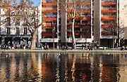 Buildings and pedestrians along the Quai de Jemappes on the Canal Saint-Martin, in the 10th arrondissement of Paris, France. The Canal Saint-Martin is a 4.6km long waterway between the Canal de l'Ourcq and river Seine, built 1802-25 to provide a fresh water source to the city and provide a trade route for canal barges. Picture by Manuel Cohen