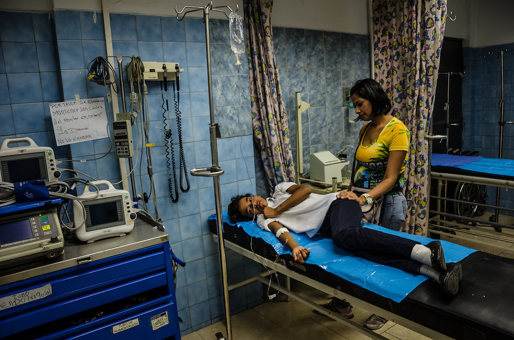 CARACAS, VENEZUELA - JANUARY 21, 2015: Maria Pulido, 10, recovers from an asprin over-dose in the pediatric emergency room inside a state hospital in the Petare slum in Caracas.  Doctors at the hospital said they are working with a bare minimum of supplies, and often have to turn patients away. Despite being a petro-state with one of the largest oil reserves in the world, basic and advanced medical supplies from gauze and surgical gloves, to heart stints, are difficult to find in hospitals and pharmacies across Venezuela.