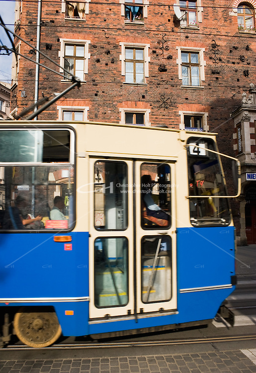 Blue tram passes House Under The Spider building by Teodor Talowski on 35 Ulica Karmelicka in Krakow Poland