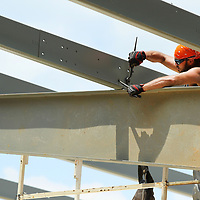 Jon Fisher, a worker with Southland Construction in Tupelo, tightens down bolts as he secures a roofing beam on the new construction of the homeless shelter, The Red Shield Lodge, at the Salvation Army in Tupelo on Tuesday afternoon.