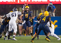 Sep 5, 2015; Morgantown, WV, USA; West Virginia Mountaineers quarterback Skyler Howard makes a complete pass to running back Wendell Smallwood during the second quarter against the Georgia Southern Eagles at Milan Puskar Stadium.  Mandatory Credit: Ben Queen-USA TODAY Sports