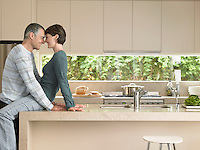 Smiling couple flirting in kitchen