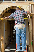 Construction worker measuring half constructed doorway with tape measure