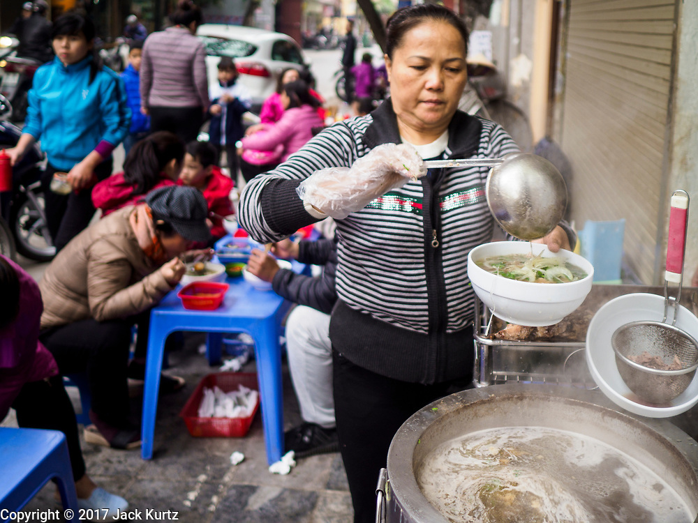 """22 DECEMBER 2017 - HANOI, VIETNAM: A woman makes """"pho,"""" Vietnamese beef noodle soup, at her street stand in the old quarter of Hanoi. The old quarter is the heart of Hanoi, with narrow streets and lots of small shops but it's being """"gentrified"""" because of tourism and some of the shops are being turned into hotels and cafes for tourists and wealthy Vietnamese.    PHOTO BY JACK KURTZ"""