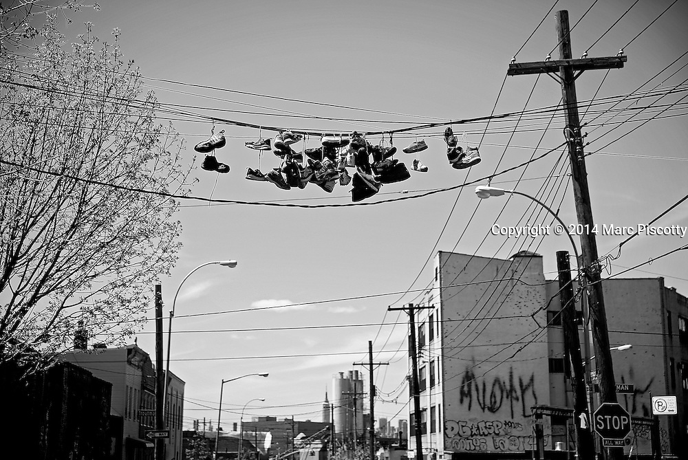 SHOT 5/5/14 11:58:40 AM - Sneakers hand from a telephone line in Bushwick. Bushwick is a rapidly gentrifying working- and middle-class neighborhood in the northern part of the New York City borough of Brooklyn. New York is the most populous city in the United States and the center of one of the most populous urban agglomerations in the world—the New York metropolitan area. The city is referred to as New York City or the City of New York to distinguish it from the State of New York, of which it is a part. A global power city, New York exerts a significant impact upon commerce, finance, media, art, fashion, research, technology, education, and entertainment. New York City has often been described as the cultural and financial capital of the world. (Photo by Marc Piscotty / © 2014)