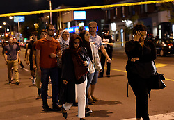 Civilians are escorted from the scene of a mass casualty incident in Toronto, ON, Canada on Sunday, July 22, 2018. A young woman has been killed and 13 others injured in a shooting incident in Toronto, Canadian police say. The Sunday night shooting happened in the Danforth and Logan avenues area. The gunman died in an exchange of fire. Among those injured is a young girl, described as in a critical condition. Police are appealing for witnesses. Photo by Nathan Denette/ABACAPRESS.COM
