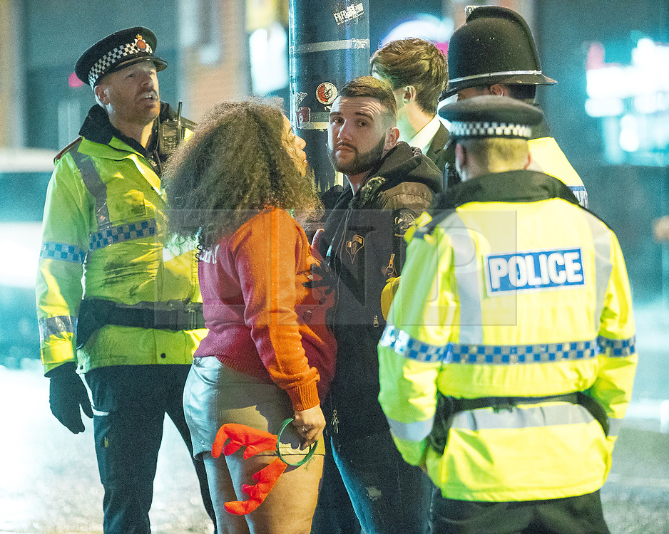 """© Licensed to London News Pictures . 23/12/2017. Manchester, UK. Police handcuff and detain a man after intervening to break up a fight . Revellers out in Manchester City Centre overnight during """" Mad Friday """" , named for being one of the busiest nights of the year for the emergency services in the UK . Photo credit: Joel Goodman/LNP"""