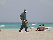 Worker taking some washed up wood from the beach Miami USA