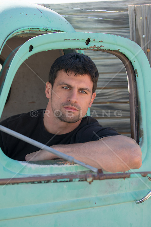 All American man with green eyes and dark hair sitting in a pick up truck