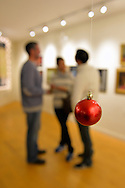Huntington, New York, USA. February 20, 2014. Beyond a red Christmas Ball ornament hanging from the ceiling, a trio of friends talk at the Jingle Boom Holiday Bash, at the festively decorated Main Street Gallery of Huntington Arts Council.