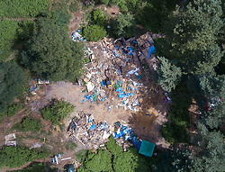 © Licensed to London News Pictures. 20/03/2017. Dorking, UK. An aerial photograph shows the remains of fort built by protestors after bailiffs dismantled it near Leith Hill. Workers are dismantling a protest fort built over an oil well site near Leith Hill in the North Downs . Protestors have been evicted from the camp over the last few days. Planning permission for 18 weeks of exploratory drilling was granted to Europa Oil and Gas in August 2015 after a four-year planning battle. The camp was set up by protestors in October 2016 in order to draw attention to plans to drill in this Area of Outstanding Natural Beauty (AONB) in the Surrey Hills. The camp has received support from the local community. Photo credit: Peter Macdiarmid/LNP