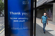 During the UK's Coronavirus pandemic lockdown and on the day when a further 255 deaths occurred, bringing the official covid deaths to 37,048, <br /> a pedestrian walks past a digital ad thanking NHS staff (National Health Service) at a bus stop on Oxford Street, on 26th May 2020, in London, England.