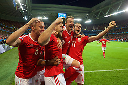 LILLE, FRANCE - Friday, July 1, 2016: Wales' Sam Vokes [2nd from R] celebrates scoring the third goal against Belgium to seal a 3-1 victory, with team-mates Andy King, Chris Gunter and Gareth Bale during the UEFA Euro 2016 Championship Quarter-Final match at the Stade Pierre Mauroy. (Pic by David Rawcliffe/Propaganda)