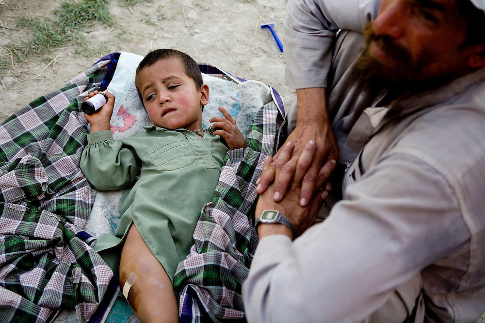 An Afghan child is treat by the 82nd Airborne after being injured by an ISAF airstrike that killed his sister near Sangin, Helmand province, Afghanistan on Saturday, April 14, 2007.