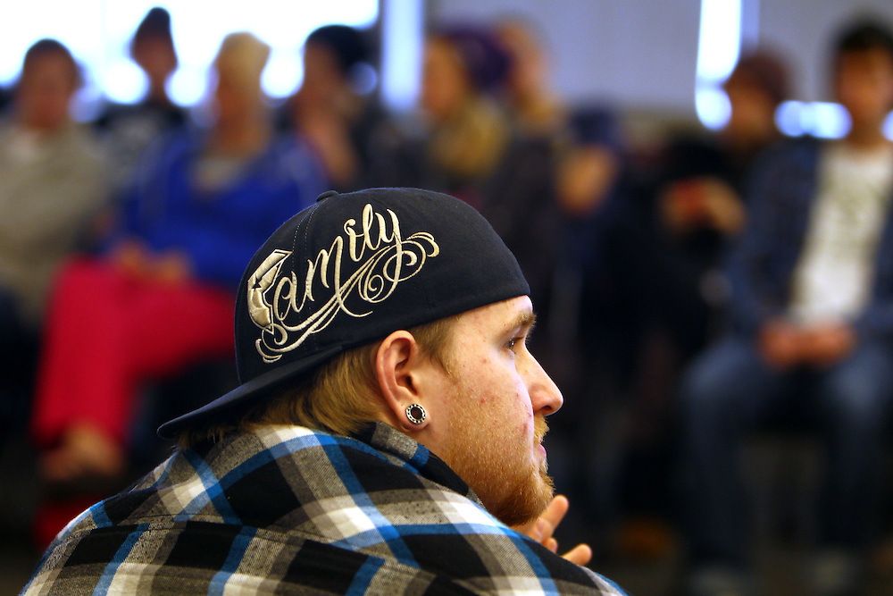 """3/7/11 5:15:13 PM -- Minneapolis, MN, U.S.A.---.James """"Bear"""" Mahowald, 21, of Hastings, MN, used the word on his hat--""""family""""--to describe what unity means to him during a StepUP all-house Circle meeting at Augsburg College in downtown Minneapolis March 7, 2011.  Residents gather weekly to discuss housing issues, talk about upcoming events and check in with each other on their journeys in recovery..---.Photo by Courtney Perry, Freelance."""