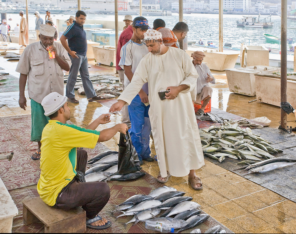 Shoppers, all men, in the Muscat fish market one morning.  One purchaser, wearing dishdasha, is paying for his purchase as the seated seller hands it over in a plastic bag.  Mattrah harbor beyond.
