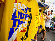 """28 NOVEMBER 2014 - BANGKOK, THAILAND: A woman in Bangkok looks at tee shirts that say """"Long Live the King"""" before the King's Birthday in Thailand. Bhumibol Adulyadej, the King of Thailand, was born on December 5, 1927, in Cambridge, Massachusetts. The family was in the United States because his father, Prince Mahidol, was studying Public Health at Harvard University. He has reigned since 1946 and is the world's currently reigning longest serving monarch and the longest serving monarch in Thai history. Bhumibol, who is in poor health, is revered by the Thai people. His birthday is a national holiday and is also celebrated as Father's Day. He is currently hospitalized in Siriraj Hospital, recovering from a series of health setbacks. Thousands of people come to the hospital every day to sign get well cards for the King. People wear yellow at events associated with the King because he was born on a Monday, and yellow is Monday's color in Thai culture. It's also the color of the monarchy.       PHOTO BY JACK KURTZ"""