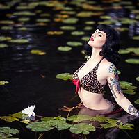 Woman with tattoos wearing lepard bikini taking a bath in a dark lake with lilies