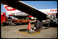 Worker pumps fuel from underground tank to TWA jet on tarmac; Lambert Intl Airport, St. Louis. Missouri