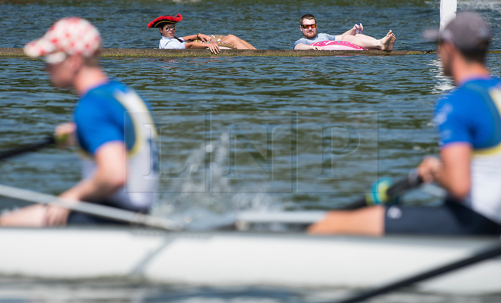 © Licensed to London News Pictures. 04/07/2018. Henley-on-Thames, UK. Two men in inflatables watch day one of the Henley Royal Regatta, set on the River Thames by the town of Henley-on-Thames in England. Established in 1839, the five day international rowing event, raced over a course of 2,112 meters (1 mile 550 yards), is considered an important part of the English social season. Photo credit: Ben Cawthra/LNP
