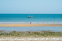 Bridlington North Beach A couple walk down the beach past a  Yacht sitting out in the bay<br />