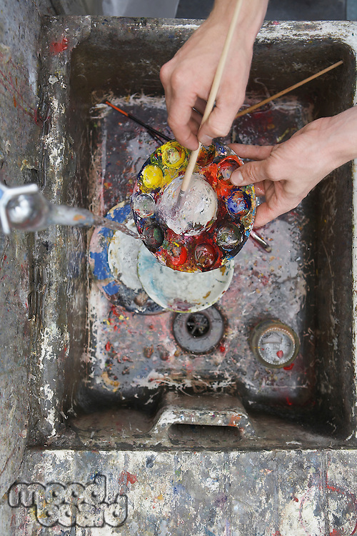 Artist rinsing palette at sink in studio view from above close-up of hands
