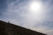 Silhouette of people walking down the steep slope mountainside Pen Y Fan in Brecon Beacons National Park, Wales, Powys, United Kingdom. Pen Y Fan is the highest point in the Brecon Beacons hill and mountain range in South Wales. The National Park was established in 1957 due to the spectacular landscape which is rich in natural beauty and is run by the National Trust.  (photo by Andrew Aitchison / In pictures via Getty Images)