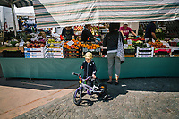 TOSCOLANO MADERNO, ITALY - 19 APRIL 2018: A child eats a strawberry by a fruits and vegetables stand at the Thursday market in Toscolano Maderno, Italy, on April 19th 2018.<br /> <br /> Lake Garda is the largest lake in Italy. It is a popular holiday location located in northern Italy, about halfway between Brescia and Verona, and between Venice and Milan on the edge of the Dolomites. The lake and its shoreline are divided between the provinces of Verona (to the south-east), Brescia (south-west), and Trentino (north).