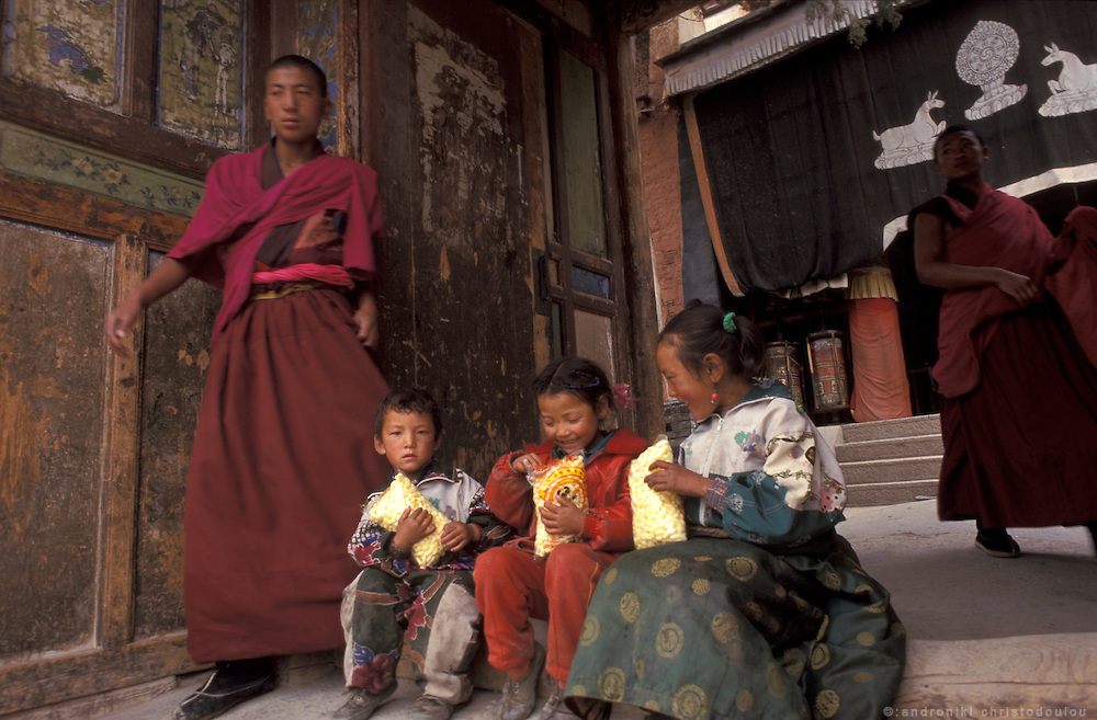 Monks offer snacks to the children..LAMBRANG MONASTERY IN XIAHE - CHINA.copyright: Androniki Christodoulou.