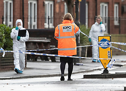 © Licensed to London News Pictures. 03/12/2018. London, UK. An investigator from the Independent Office for Police Conduct (IOPC) talks to officers near the scene in Wimbledon where a man was shot by police on a pre-planned operation this morning. Photo credit: Peter Macdiarmid/LNP