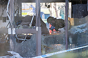 © Licensed to London News Pictures. 15/01/2015. Crowmarsh, UK. A bomb disposal officer insects a burnt out vehicle in the main reception of the building.  Fire has engulfed council offices in Oxfordshire and two other buildings following a spate of suspected arson attacks overnight. A 47-year-old man has been arrested following the blaze at the South Oxfordshire District Council building in Crowmarsh Gifford.. Photo credit : Stephen Simpson/LNP