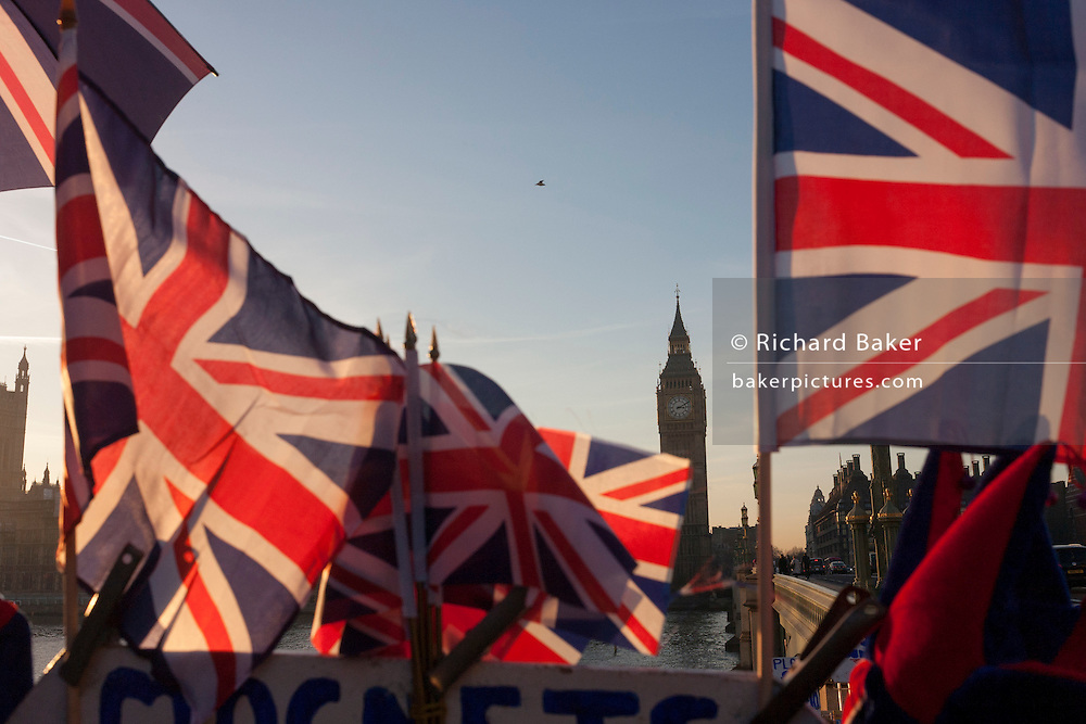 British union jack flags are in the foreground with Big Ben and the Houses of Parliament in the distance, on 30th November 2016, in London, England.