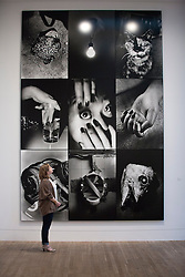 © Licensed to London News Pictures. 08/10/2012. LONDON, UK. A member of Tate staff views a huge collage entitled 'Memory 2012' (2012) by artist Daido Moriyama at an exhibition at the Tate Modern in London today (08/10/12). The exhibition, entitled 'William Klein + Dado Moriyama', is the first to examine the relationship between the work of photographer/film maker William Klein (b. 1928) and photographer Dado Moriyama (b. 1938) and opens to the public on the 10th of October 2012.  Photo credit: Matt Cetti-Roberts/LNP