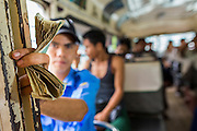 19 JUNE 2013 - YANGON, MYANMAR: A Yangon bus conductor holds the fare money he's collected on his shift. Yangon buses are generally overcrowded and in poor repair but as the economy improves newer, but still used, Japanese and Korean buses are being imported. Hundreds of bus routes criss-cross Yangon, providing the cheapest way of getting around the city. Most fares are less than the equivalent of .20¢ US.   PHOTO BY JACK KURTZ