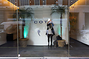 A woman stands in the entrance to the Coty office and prepares her face using a mirror before attending a meeting.