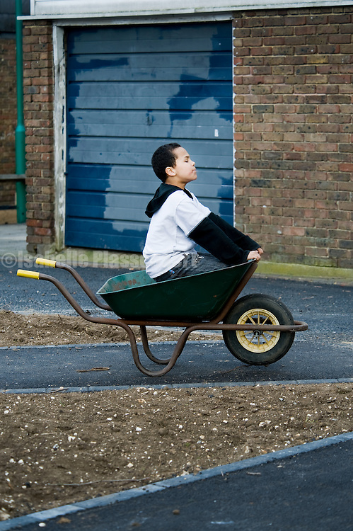 Jason Jones, model released at Blenheim gardens, an urban agriculture initiative led by Bonnie Hewson, kids preparing beds to grow vegetables on a run down council estate in Brixton
