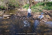 Little Boy and Baby Girl Playing Throwing Pebbles into the River, Hathersage, Peak District, Derbyshire, UK