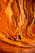 "Professsional climber Steph Davis ""bouldering"" (unroped rock climbing) on sandstone near Moab Utah, USA.,"