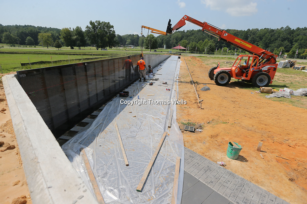Phillip Taylor and Roger Cole of Intrepid Stone and Marble from Harvey Louisiana begin to install the first marble walls for the Vietnam War Memorial under construction at Veterans Park in Tupelo.