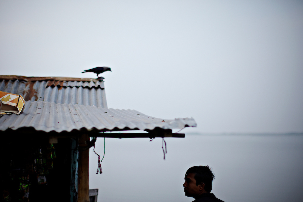 A man and a crow on the northern shore of Bhola..This area in the south of Bangladesh has been called ground zero of climate-change due to heavy river and ocean erosion. The lowlying area is also hugely affected by cyclones and rising sea-levels...By the Mouth of Ganges, at the Bay of Bengal is the Island of Bhola. This home of about two million people is considered to be ground zero of climate change. Half the island has disappeared in the past 40 years, and according to scientists the pace is not going to slow down. People pack up and leave as the water get closer. Some to a nearby embankment, while those with enough money move further inland, but for most life move on until the inevitable. It's always about survival for the people in one of the worlds poorest countries...Photo by: Eivind H. Natvig/MOMENT