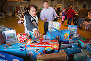 Lucena Penaloza of Milpitas selects toys for her daughters with the help of volunteer Nick Guglielmelli during a Milpitas Fire Department toy drive at Genesis United Methodist Church in Milpitas, California, on December 21, 2013. (Stan Olszewski/SOSKIphoto)