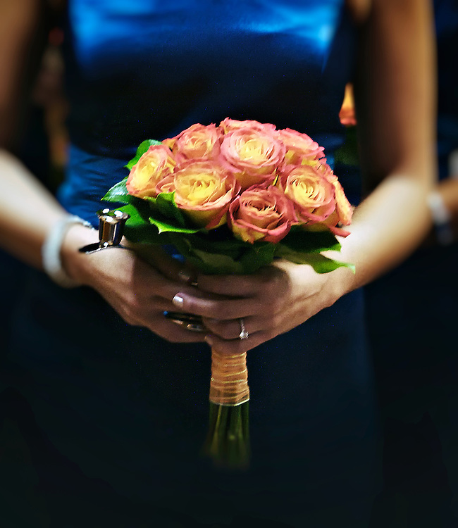 Woman in blue dress holds a bouquet of red and yellow roses.