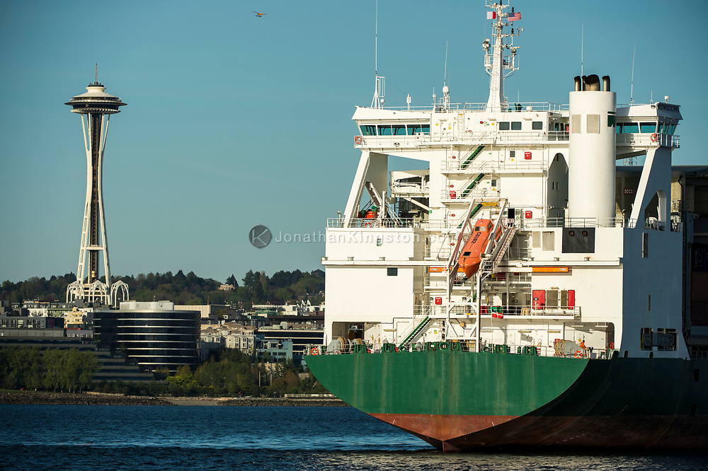 A container ship pulling into the port of Seattle, Washington with the Space Needle visible in the background.